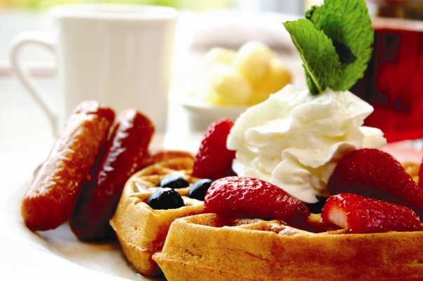 Blueberry waffles with maple syrup, topped with whipped cream and mint leaf. Served with fresh strawberries and sausages on the side.